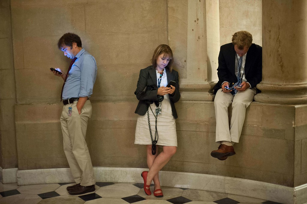 . Reporters check their smartphones while waiting outside US House Speaker John Boehner\'s office at the US Capitol in Washington on September 30, 2013 as a possible government shutdown looms.     AFP PHOTO/Nicholas KAMM/AFP/Getty Images
