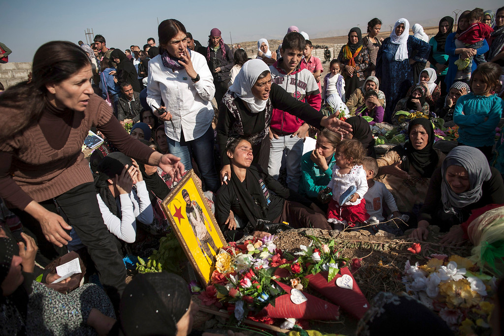 . Kurdish family and friends visit the Martyrs\' cemetery to remember those who died in Syria\'s civil war on October 15, 2013, in Syria\'s Kurdish town of Derik (al-Malikiyah in Arabic), on the first day of Eid al-Adha, which commemorates the willingness of Abraham to sacrifice his son at God\'s command.  AFP PHOTO/STR-/AFP/Getty Images