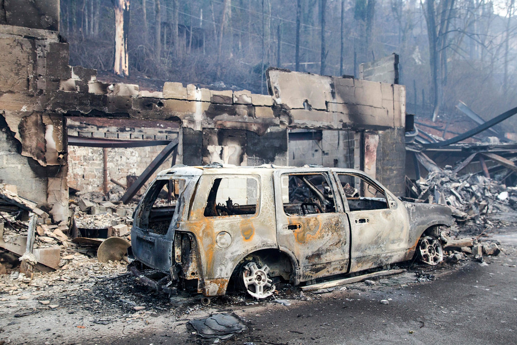 . A scorched vehicle sits next to a burned out building in Gatlinburg, Tenn., on Tuesday, Nov. 29, 2016. The fatal fires swept over the tourist town the night before, causing widespread damage. (AP Photo/Erik Schelzig)