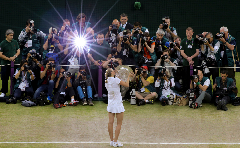 Description of . Petra Kvitova of Czech Republic poses with  the trophy in front of photographers after winning the women\'s singles final against Eugenie Bouchard of Canada at the All England Lawn Tennis  Championships at Wimbledon, London, Saturday, July, 5, 2014. (AP Photo/Gareth Fuller, Pool)