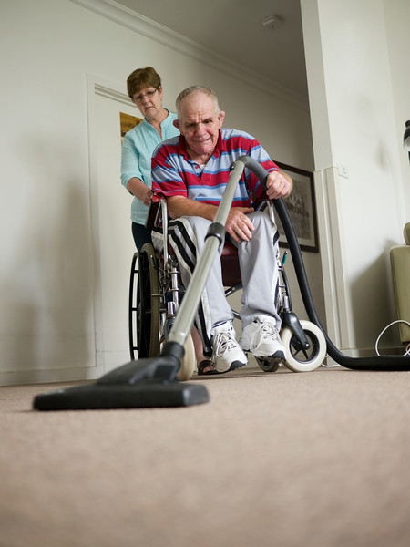 """This photo shows a senior man with an intellectual and physical disability vacuuming the floor of his home.  He is being assisted by a home carer.  This photo can be used to illustrate the importance of promoting engagement in meaningful activity.  This whole concept and practice has been referred to as Person-Centred Active Support and has extensive empirical evidence to support its importance in promoting a great quality of life for all people with a disability, """"irrespective of degree of disability or the presence of extra problems*  * Mansell, J., Beadle-Brown, J., Ashman, B., & Ockenden, J. (2004). Person-Centred Active Support. Pavilion Publishing (Brighton) Ltd.."""