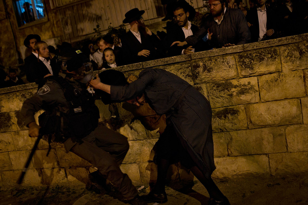 . An Israeli security officer scuffles with an ultra-orthodox Jew during a protest against military conscription of yeshiva students, in Jerusalem, Thursday, May 16, 2013. (AP Photo/Bernat Armangue)