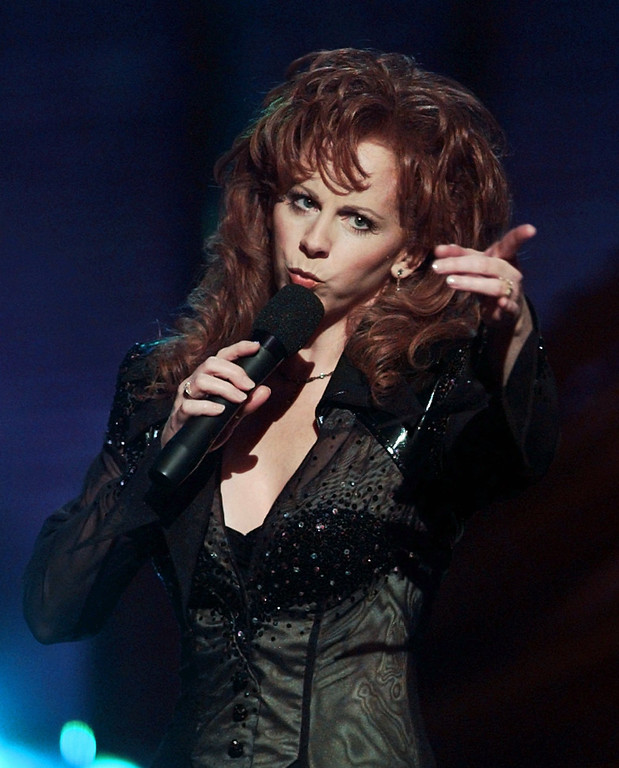 ". Country music star Reba McEntire gestures during a performance of ""Starting Over Again\"" at the 31st Annual Academy of Country Music Awards Wednesday, April 24, 1994 at the Universal Amphitheatre in Universal City, Calif. (AP Photo/Susan Sterner)"
