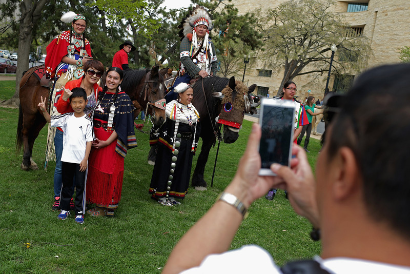 ". Members of the Sicangu Lakota Band of the Rosebud Sioux Tribe from Rosebud, South Dakota, pose for photographs with tourists from Chinga before a demonstration against the proposed Keystone XL pipeline outside the National Museum of the American Indian April 22, 2014 in Washington, DC. As part of its ""Reject and Protect\"" protest, the Cowboy and Indian Alliance is organizing a weeklong series of actions by farmers, ranchers and tribes to show their opposition to the pipeline.  (Photo by Chip Somodevilla/Getty Images)"