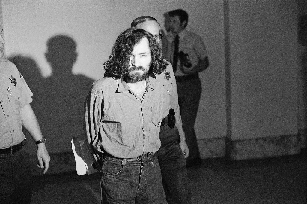 . Charles M. Manson, squinting in the glare of a film cameraman\'s floodlight, marches to court, Aug. 20, 1970, for a hearing on his claim he is being mistreated by deputies in the Los Angeles County Jail.  After the hearing his trial on murder charges resulting from the slayings of actress Sharon Tate and six others was scheduled to resume. (AP Photo/George Brich)