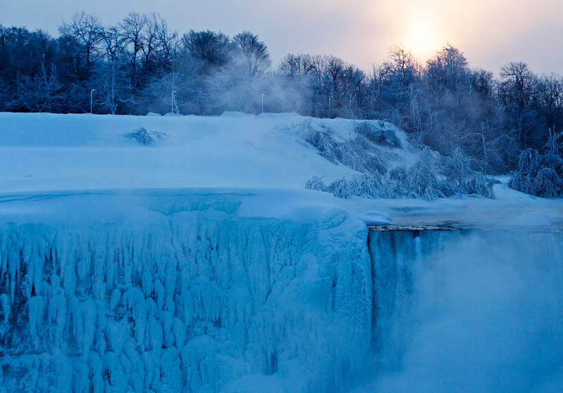 . The sun rises over masses of ice formed around the Canadian \'Horseshoe\' Falls in Niagara Falls, Ontario, Canada, Thursday, Feb. 19, 2015. (AP Photo/The Canadian Press,Aaron Lynett)