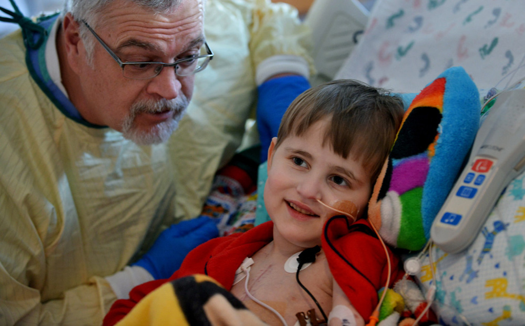 """. \""""My name is Clifford, too,\"""" said respiratory therapist Bob Clifford, left, who draws a smile from Cameron Ulrich as he watches his favorite cartoon, \""""Clifford the Big Red Dog,\"""" in his room.   (Pioneer Press: Richard Marshall)"""