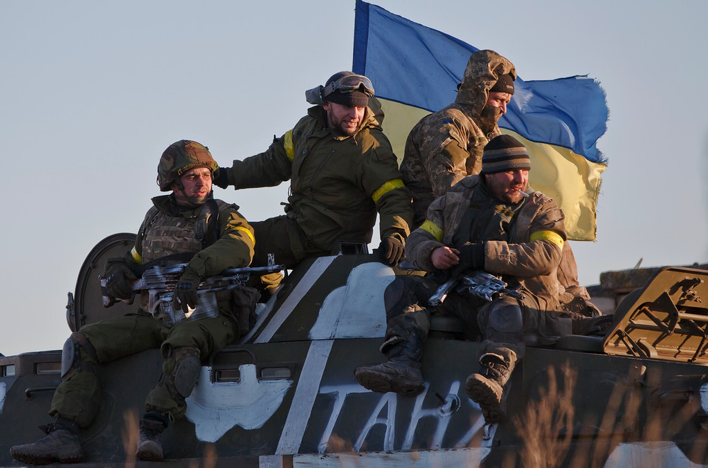 . Ukrainian troops ride on an armored vehicle outside Artemivsk, Ukraine, while pulling out of Debaltseve, Wednesday, Feb. 18, 2015. After weeks of relentless fighting, the embattled Ukrainian rail hub of Debaltseve fell Wednesday to Russia-backed separatists, who hoisted a flag in triumph over the town. The Ukrainian president confirmed that he had ordered troops to pull out and the rebels reported taking hundreds of soldiers captive.(AP Photo/Vadim Ghirda)