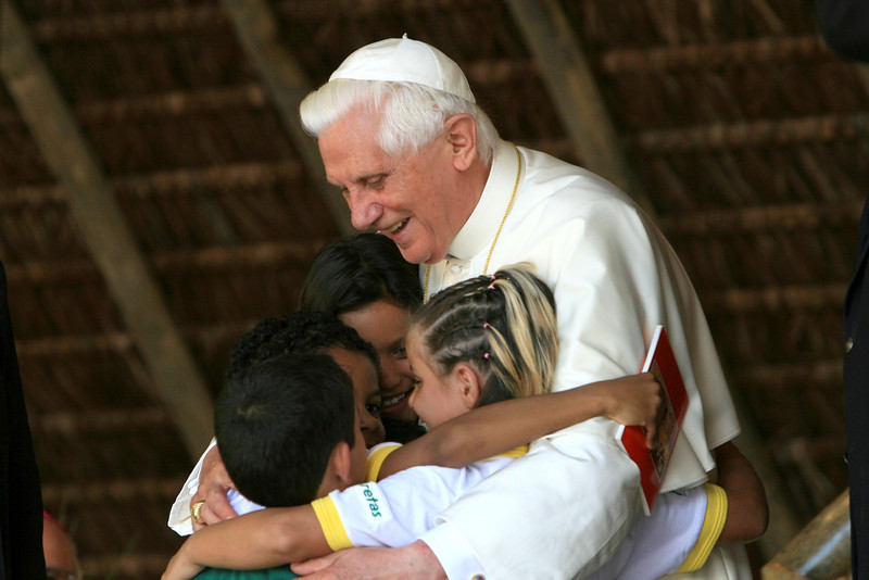 . Pope Benedict XVI has announced that he is to resign on February 28, 2013 GUARANTIGUETA, BRAZIL - MAY 12:  Pope Benedict XVI embraces children during a visit at the Fazenda da Esperanca, a facility for recovering drug addicts, May 12, 2007 in Guaratingueta, Brazil. The pope is on a five-day visit to Brazil.  (Photo by Franco Origlia/Getty Images)