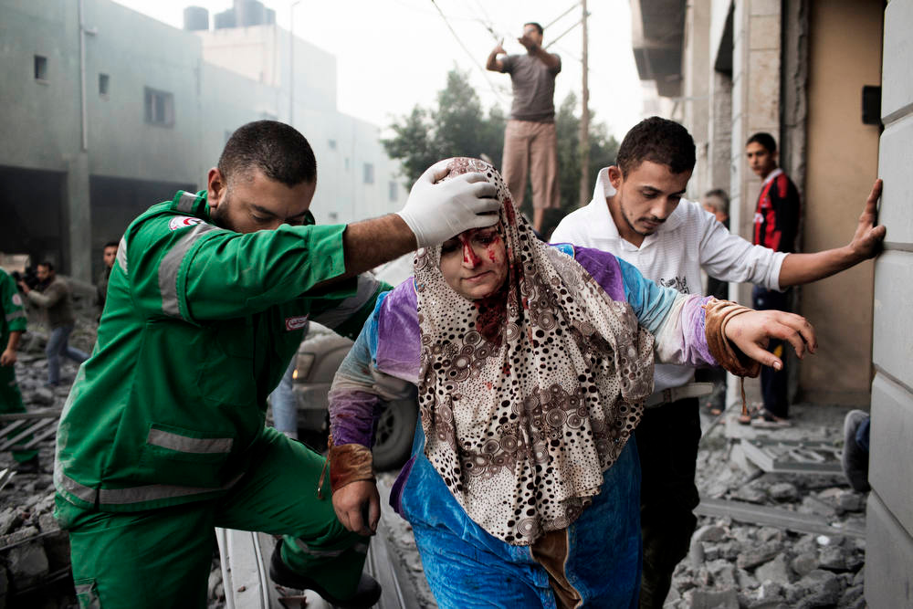 Description of . A Palestinian woman is helped by a paramedic out of her building, damaged during an Israeli air raid on a nearby sporting centre in Gaza City November 19, 2012.   Israeli air strikes on Sunday killed 31 Palestinians in the bloodiest day so far of its air campaign on the Gaza Strip, as diplomatic efforts to broker a truce intensified.   AFP PHOTO/MARCO  LONGARI/AFP/Getty Images