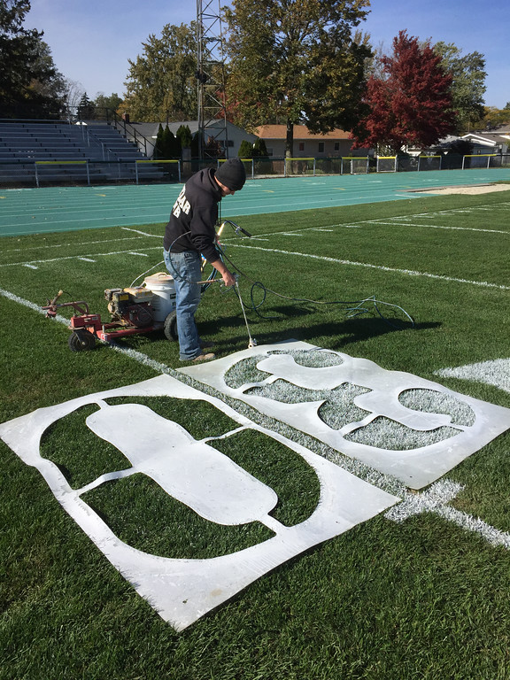 . Andrew Kirschner paints the yard markers on the Marion L. Steele Football Field prior to game day. (Chuck Grimmett - Amherst Exempted Village School District)