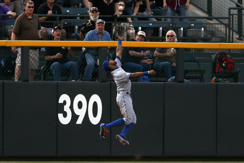 . DENVER, CO - MAY 03:  Left fielder Chris Young #1 of the New York Mets leaps to catch a fly ball by Carlos Gonzalez #5 of the Colorado Rockies to end the first inning at Coors Field on May 3, 2014 in Denver, Colorado.  (Photo by Doug Pensinger/Getty Images)