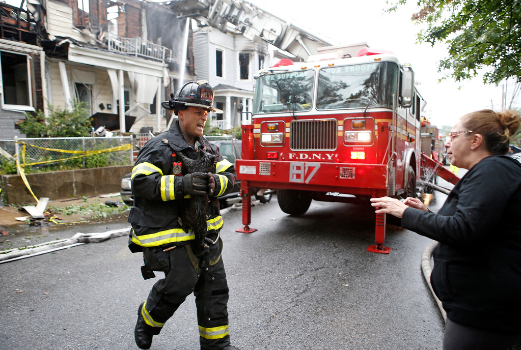 . Firefighter Lou Femia, left, delivers a cat named Zack to his owner Cindy Piscopo after a fire destroyed Piscopo\'s home in a townhouse in the Staten Island borough of New York, Thursday, June 5, 2014.   (AP Photo/Kathy Willens)