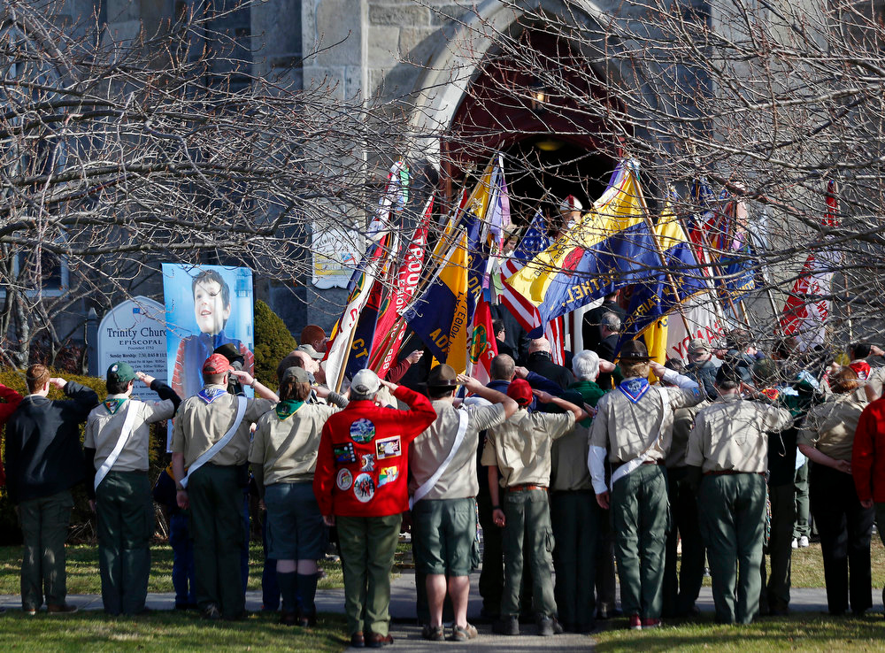 . People wearing Boy Scouts of America uniforms salute while standing outside of Trinity Episcopal Church during funeral services for Benjamin Andrew Wheeler, Thursday, Dec. 20, 2012, in Newtown, Conn. Wheeler, 6, died when the gunman, Adam Lanza, walked into Sandy Hook Elementary School in Newtown, Dec. 14, and opened fire, killing 26 people, including 20 children, before killing himself. (AP Photo/Julio Cortez)