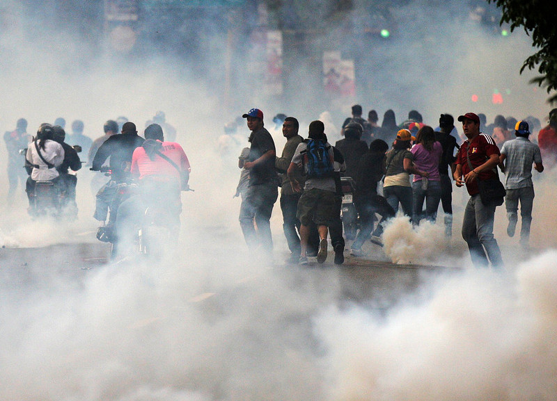 . Supporters of opposition leader Henrique Capriles run from tear gas fired by riot police as they demonstrated for a recount of the votes in Sunday\'s election, in Caracas, April 15, 2013. Hundreds of protesters clashed with police in the Venezuelan capital on Monday after Capriles called for demonstrations to demand a recount of votes from Sunday\'s election to replace the late Hugo Chavez. REUTERS/Christian Veron