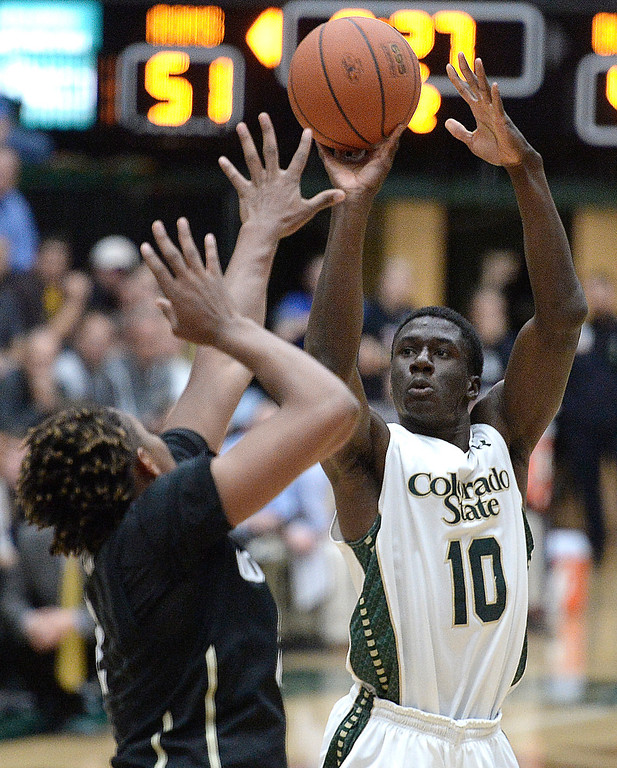 . CSU\'s Joe De Ciman takes a shot over Xavier Johnson during an NCAA game against CU on Tuesday, Dec. 3, 2013, at the Moby Arena in Fort Collins. Jeremy Papasso/ Camera