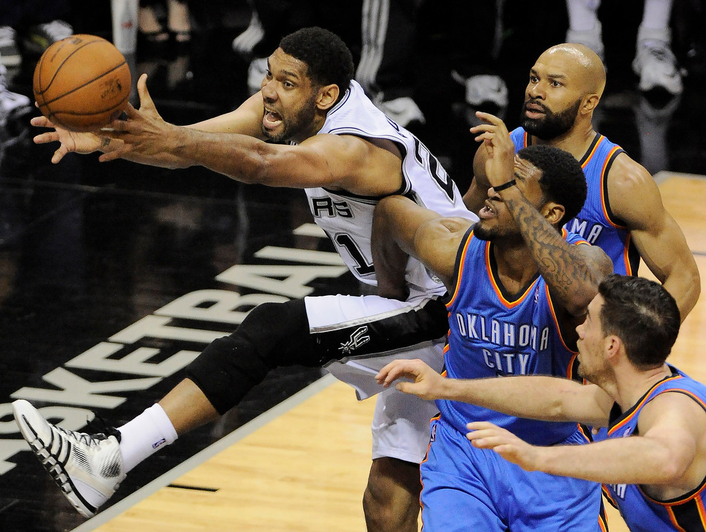 . San Antonio Spurs forward Tim Duncan, left, chases the loose ball against Oklahoma City Thunder\'s Nick Collison, right, Perry Jones, and Derek Fisher, right rear, during the first half of Game 2 of the Western Conference finals NBA basketball playoff series, Wednesday, May 21, 2014, in San Antonio. (AP Photo/Darren Abate)
