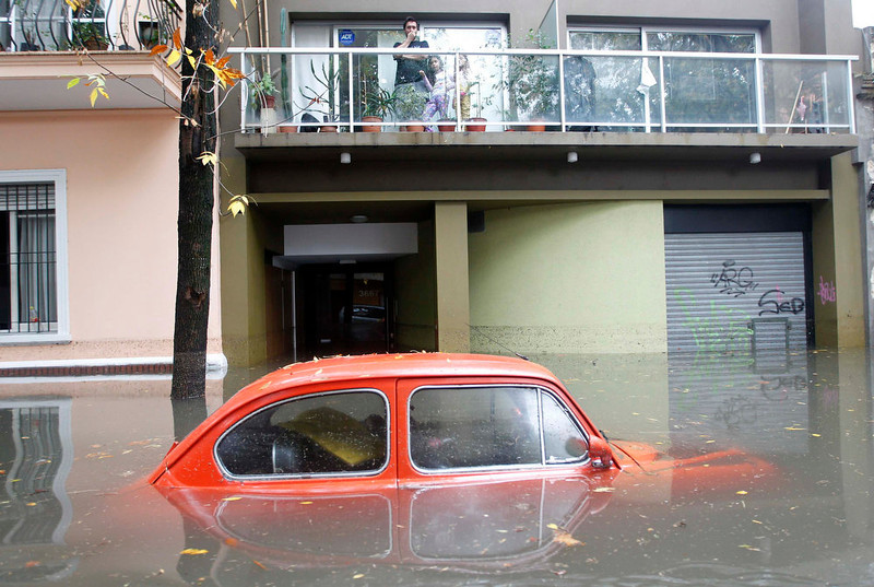 . Residents look at a submerged car in a flooded street after a rainstorm in Buenos Aires April 2, 2013. Thunderstorms damaged property and vehicles, cut power and caused delays on flights in Buenos Aires and its suburbs. The City\'s SAME emergency service announced that the death toll has risen to five.   REUTERS/Enrique Marcarian