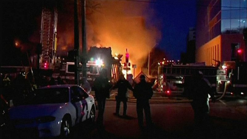 . A still image taken from a KHSB-TV video footage shows fire engines and emergency officials near the scene of the fire at Kansas City, Missouri February 19, 2013. A fire triggered by a natural gas explosion that appeared to have originated underground engulfed a restaurant in Kansas City, Missouri, on Tuesday, injuring more than a dozen people, authorities and witnesses said.  REUTERS/KHSB-TV