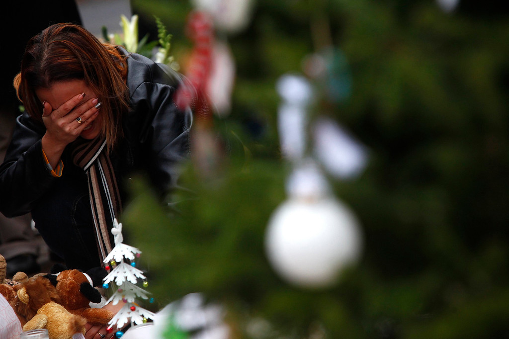 . A woman reacts at a makeshift memorial near Sandy Hook Elementary School, where a mass shooting took place, in Newtown, Connecticut December 16, 2012. Worshippers filled Sunday services to mourn the victims of a gunman\'s rampage at the school that killed 20 children and six adults with President Barack Obama due to appear later at an interfaith vigil to help this shattered Connecticut town recover. REUTERS/Eric Thayer