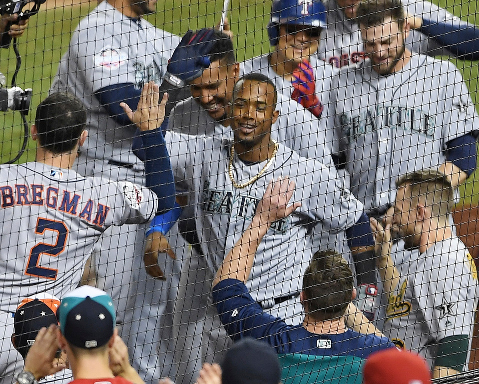 . Seattle Mariners Jean Segura (2) center, is greeted at the dugout after his three-run homer in the eighth inning during the Major League Baseball All-star Game, Tuesday, July 17, 2018 in Washington. (AP Photo/Nick Wass)
