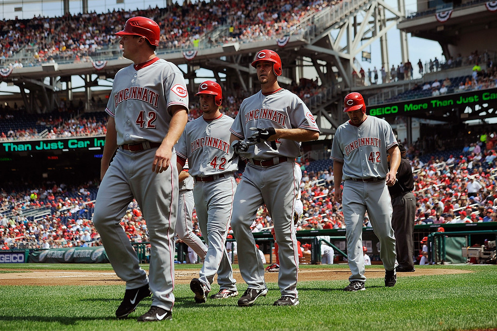 . Ryan Ludwick walks off the field with teammates Zack Cozart, Scott Rolen, and Jay Bruce after hitting a grand slam against the Washington Nationals at Nationals Park on April 15, 2012 in Washington, DC. In honor of Jackie Robinson Day, all players across Major League Baseball wore number 42. (Photo by Patrick McDermott/Getty Images)