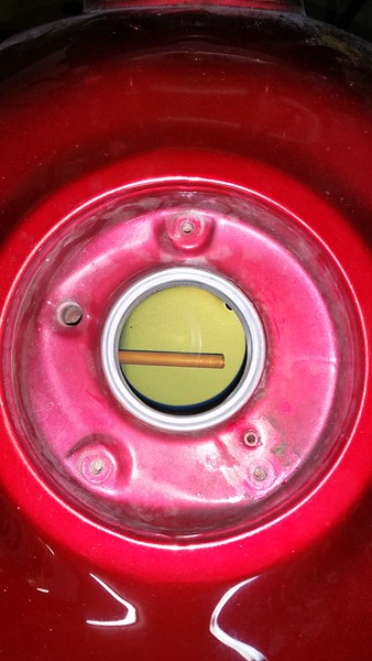 One of the problems I encountered on my little test ride across Texas was that fuel would not transfer from aux cell to main tank unless the cap was open. Venting problem. I have learned the tank can and usually does operate under some pressure.  Pressurization is not requisite but rather a byproduct of the fuel pressure regulator constantly shooting fuel from the fuel rail back into the tank and the fact that the oem cap is equipped with a flapper valve on the vent line to let air in but not out and is designed to close in a tip-over. Here's the vent line at the filler, the small opening between 4 and 5 o'clock. The larger port around 10o'clock is the overflow.