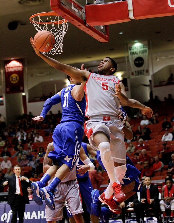 . Houston\'s guard L.J. Rose (5) is fouled by Memphis\' Michael Dixon Jr (11) as he drives to the basket during the second half of an NCAA college basketball game, Thursday, Feb. 27, 2014, in Houston. Houston won 77-68. (AP Photo/Bob Levey)