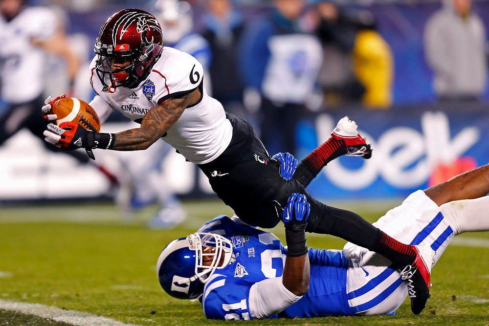 . Cincinnati\'s Anthony McClung (6) dives into the end zone for a touchdown as Duke\'s Anthony Young-Wiseman (21) defends during the first half of the Belk Bowl NCAA college football game in Charlotte, N.C., Thursday, Dec. 27, 2012. (AP Photo/Chuck Burton)