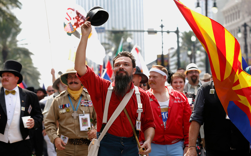 . Alexander Fleming of New Orleans tips his hat to the crowd on Canal Street during a parade which wound its way through the French Quarter kicking off the fourth annual Just For Men National Beard and Moustache Championships Saturday, Sept. 7, 2013 in New Orleans. Contestants competed in 18 different categories including Dali, full beard natural and sideburns. (AP Photo/Susan Poag)