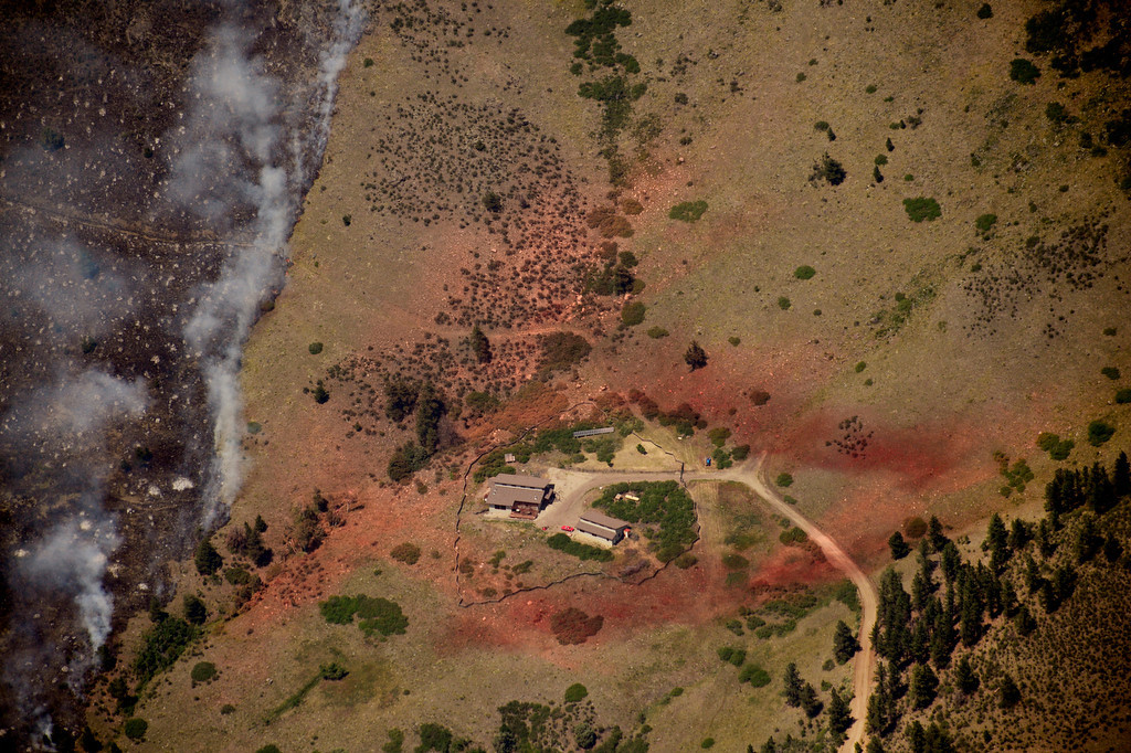 . Seen from a helicopter, a home is surrouned by slurry as the High Park Fire encroaches. Eric Lutzens, The Denver Post