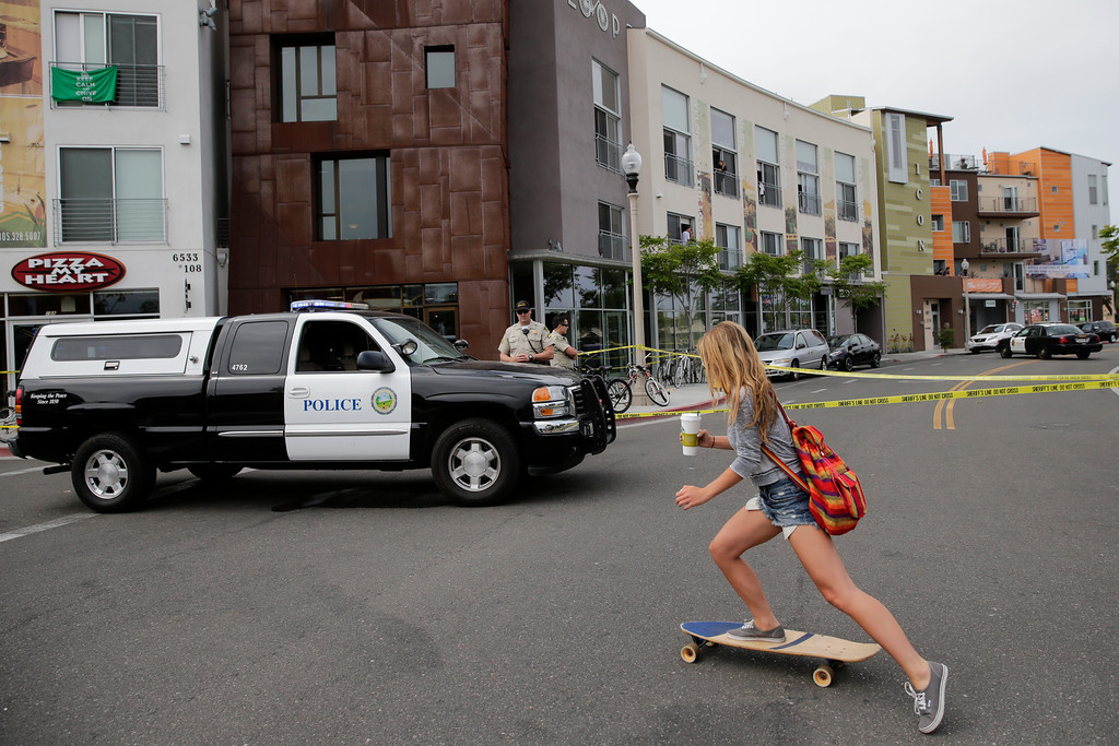 . A woman rides her skateboard past the scene of a shooting on Saturday, May 24, 2014, in Isla Vista, Calif. A drive-by shooter went on a rampage near a Santa Barbara university campus that left seven people dead, including the attacker, and others wounded, authorities said Saturday. (AP Photo/Jae C. Hong)