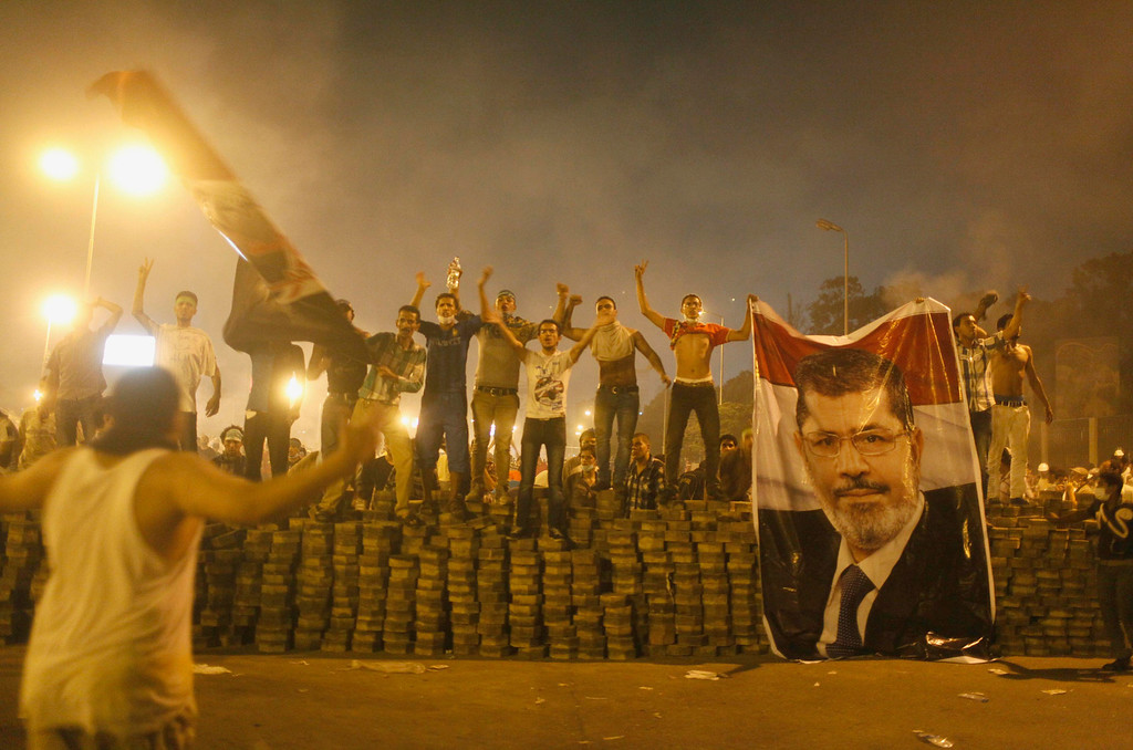 ". Supporters of deposed Egyptian President Mohamed Mursi hold a Mursi poster as they stand on a barricade built to separate them from police during clashes in Nasr city area, east of Cairo, July 27, 2013. Egyptian security forces shot dead at least 70 supporters of ousted President Mohamed Mursi on Saturday, his Muslim Brotherhood said, days after the army chief called for a popular mandate to tackle ""violence and terrorism\"". REUTERS/Asmaa Waguih"