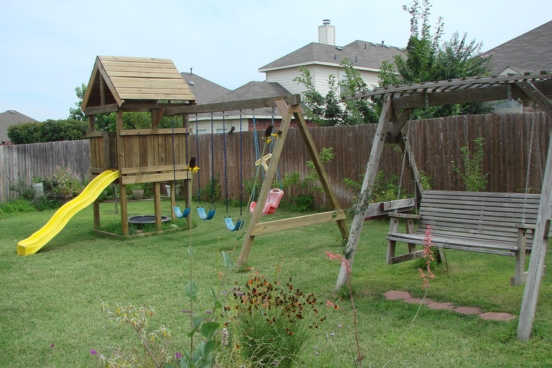 play set and swing in front of back (south) fence with island garden in foreground (6/15/07)