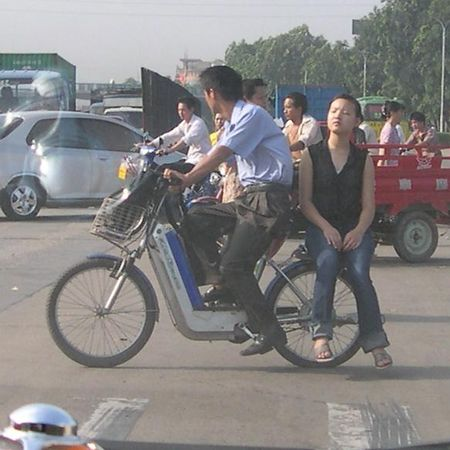 Side-saddle on a moped.