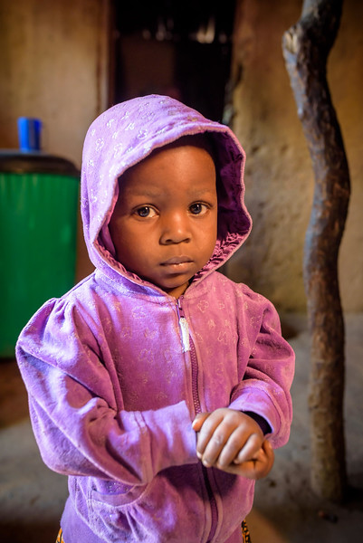 """Sweet little girl who always wore a purple hooded sweater -- Ndomba Bert, 3 yr-old cousin to Grace Mukoma, 10 yr-old boy, Kananga, Kasai Province, DRC.   Background Grace lives with his mom Mbombo Elize, 23 and an extended family of relatives. Mbombo has had 4 children, the first when she was 15. 2 died during the time they had to run away because of the war. Now it's just Grace and his sister Harriet, 7.  They live in the Kasai Centrale province in a place called Katoka. It's a rural community. Grace and his family had to run when war broke out in the DRC.  His father was killed. His mother and her 4 children ran about 2 kilometers down the road from his house towards the Lualua River. They hid there for about 3 months. Unfortunately, because of a lack of food and disease, Grace's brother and a sister died. After about 3 months Grace and his family hesitantly made their way back to their house. It had been burnt and was empty. They've struggled ever since.  Here's a look at Grace's life today:  Home Life  """"Early in the morning I sweep the compound. Then I wash and if there is food I eat. Then I join my friends at the CFS."""" """"Sometimes they send me on other errands. If they need something, they send me.""""  Food Grace's family doesn't have enough food. On any given day they may or may not eat. When they do eat, it's once a day, usually in the evening. They often go to bed hungry. At the CFS they have a feeding program. When they started it they identified 200 children who were malnourished. Grace was once of them. Today they are feeding the children a porridge made from soy, corn, which they call maize, peanuts and a fruit called maringa.  Grace eats it enthusiastically.  Water Every day, Grace follows a winding, dirt path behind his house for about a mile. It leads downhill to a muddy pond. The water is brown and has a filmy covering on it. Grace rolls up his pants and wades in with a small, purple bucket which he fills up with a smaller, stainless steel bowl.  When t"""