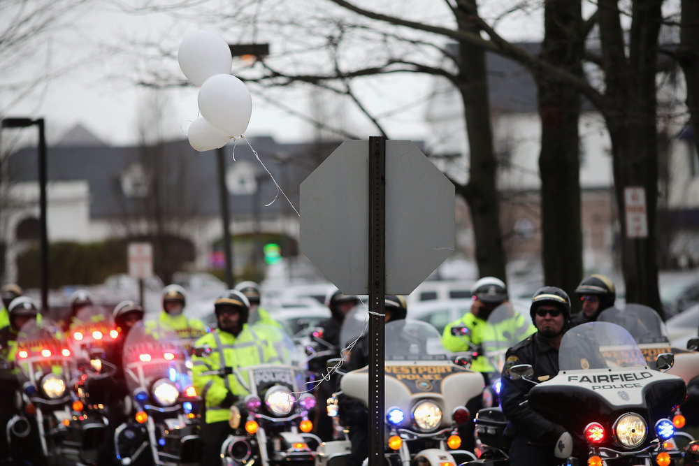 Description of . Police on motorcycles line the street following the funeral services for six year-old Noah Pozner, who was  killed in the shooting massacre in Newtown, CT, at Abraham L. Green and Son Funeral Home on December 17, 2012 in Fairfield, Connecticut. Today is the first day of funerals for some of the twenty children and seven adults who were killed by 20-year-old Adam Lanza on December 14, 2012.  (Photo by Spencer Platt/Getty Images)