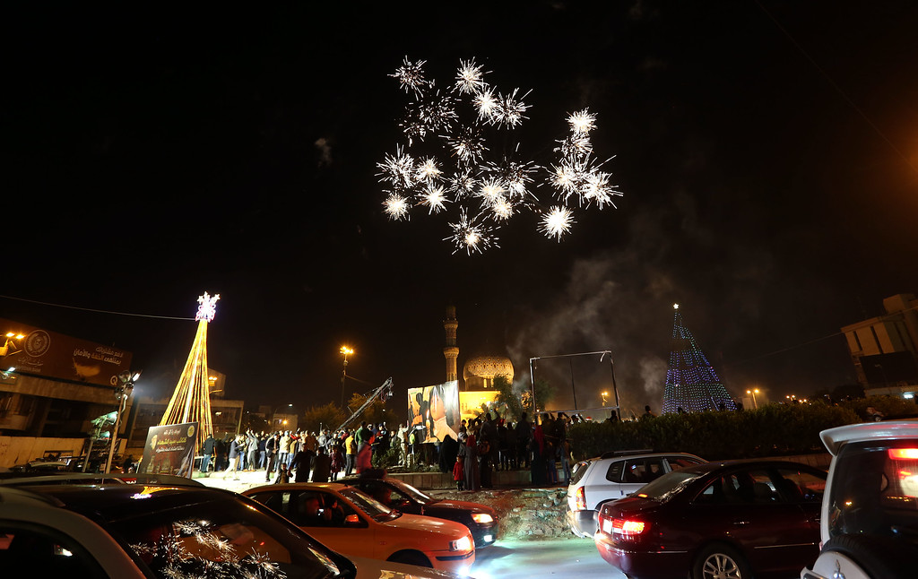 . A Iraqi Crowds cheer as the countdown and fireworks begin during a New Year\'s Day celebration at Firdous Square in Baghdad, Iraq, Wednesday, Dec. 31, 2014. (AP Photo/Hadi Mizban)