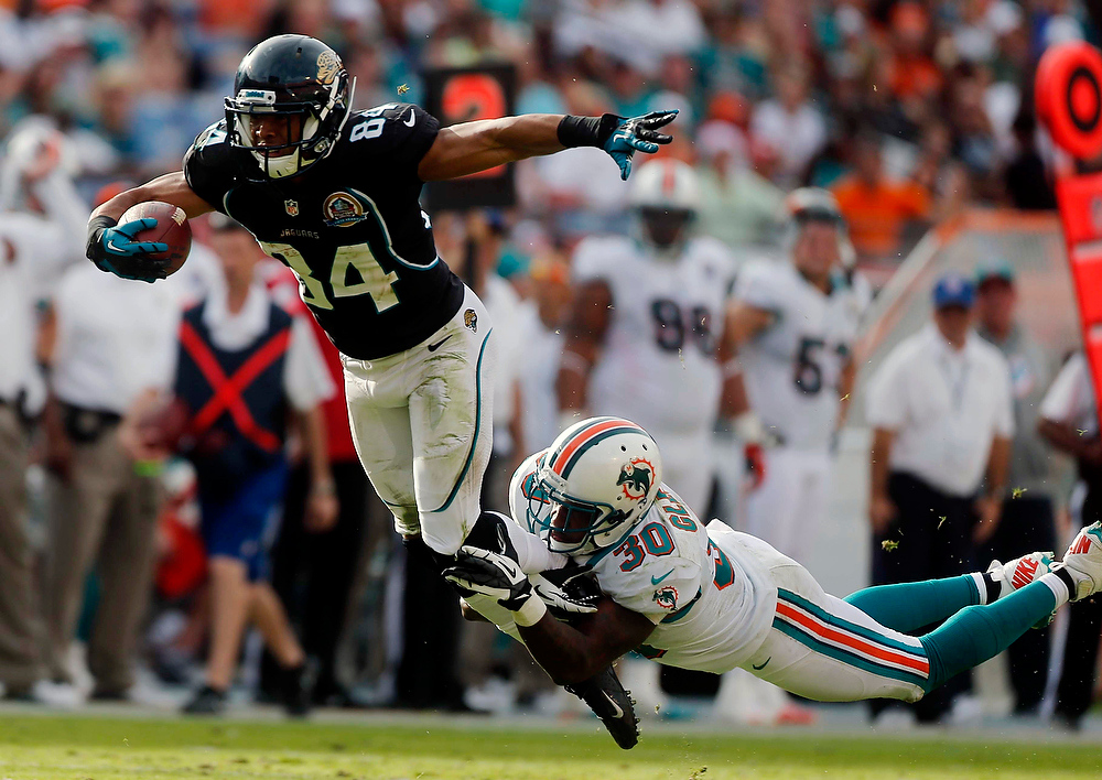 . Miami Dolphins strong safety Chris Clemons (30) tackles Jacksonville Jaguars wide receiver Cecil Shorts (84) during the second half of an NFL football game on Sunday, Dec. 16, 2012, in Miami. The Dolphins defeated the Jaguars 24-3. (AP Photo/John Bazemore)