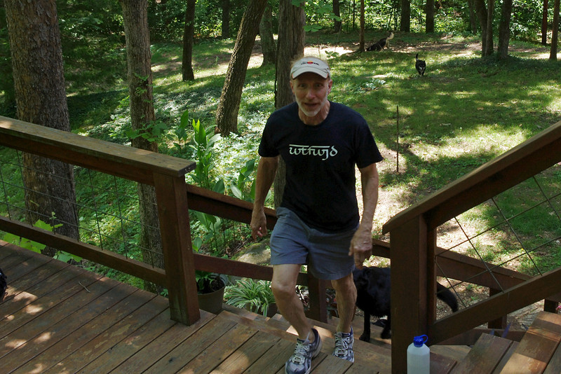 Rick Brischetto, coming up the steps to his log house.