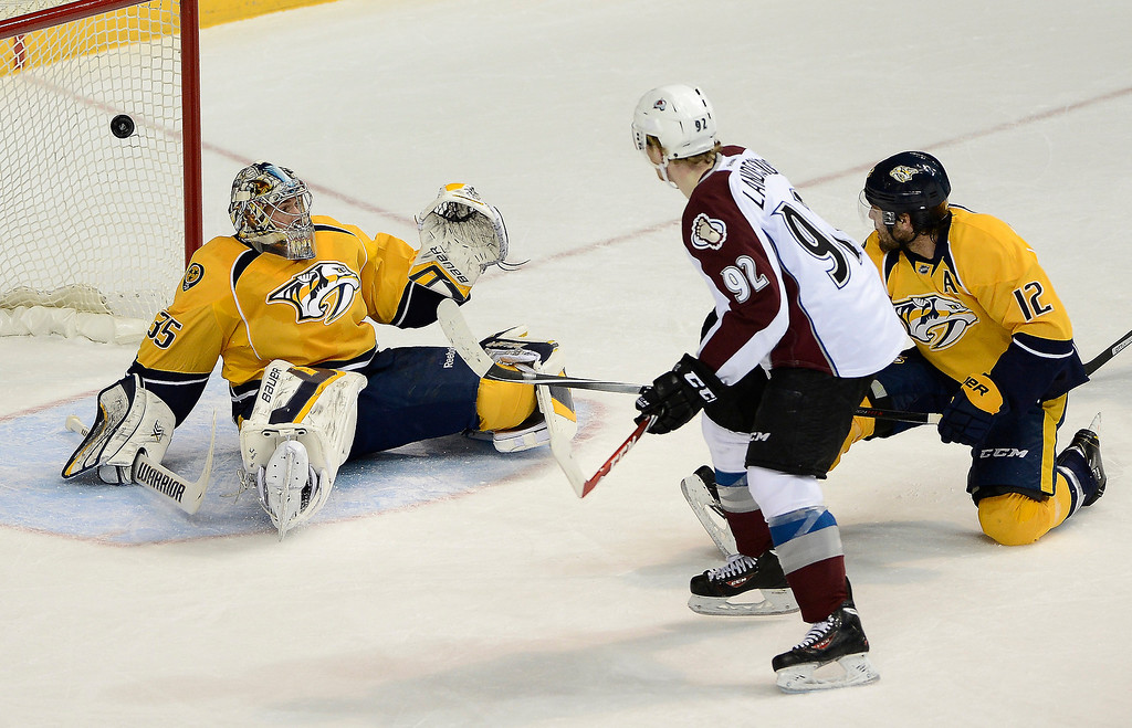 . Colorado Avalanche left wing Gabriel Landeskog (92), of Sweden, scores past Nashville Predators goalie Pekka Rinne (35), of Finland, and forward Mike Fisher (12) in the first period of an NHL hockey game on Tuesday, March 25, 2014, in Nashville, Tenn. (AP Photo/Mark Zaleski)