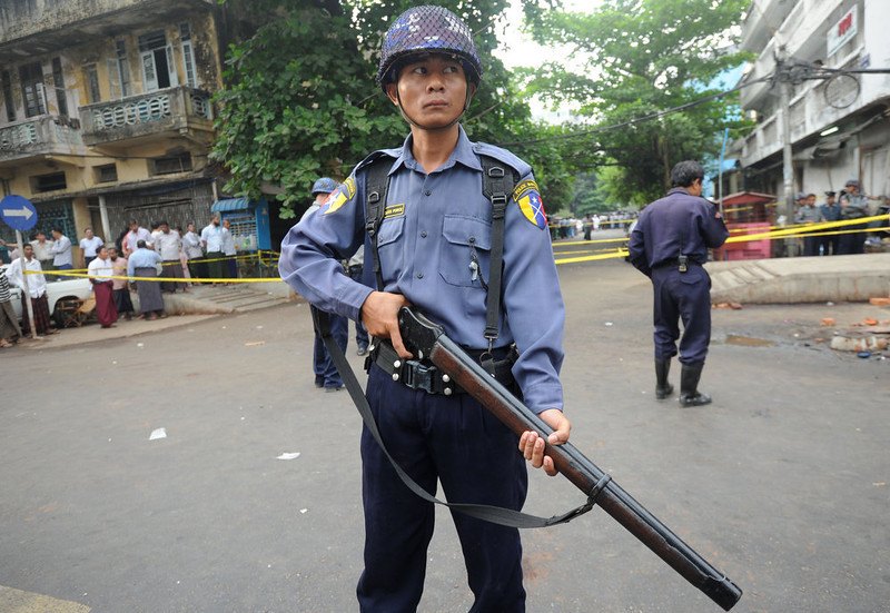 . Policemen stand guard in front of the Islamic school after a fire broke out at the school in downtown Yangon early April 2, 2013.  Thirteen people, including children, were killed after a fire broke out in a Muslim school in Yangon due to a suspected electrical fault, police in Myanmar\'s main city said.    AFP PHOTO / Soe Than WIN