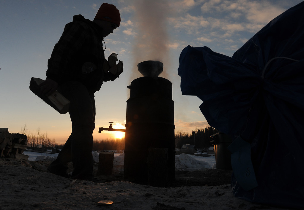 . Phil Runkle brings an armful of wood to the water heater at the Nikolai, Alaska, checkpoint during the Iditarod Trail Sled Dog Race at sunrise on Wednesday, March 5, 2014. The checkpoint provides hot water for all of the mushers. (AP Photo/Anchorage Daily News, Bob Hallinen)