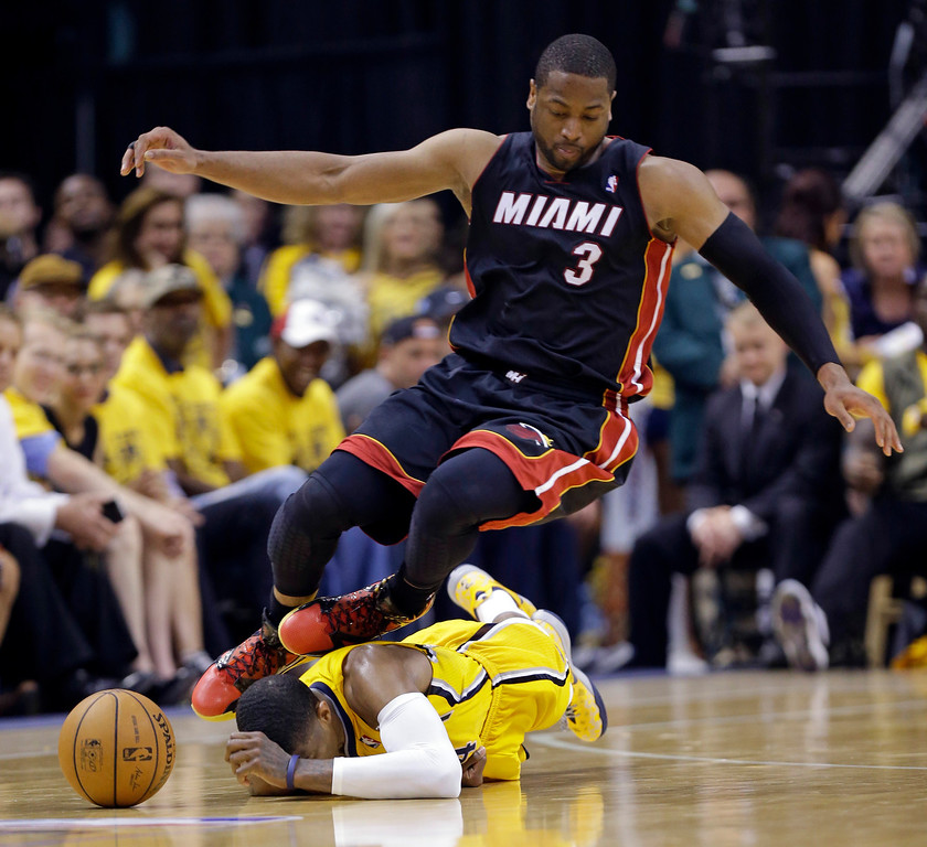 . Miami Heat guard Dwyane Wade (3) goes over Indiana Pacers forward Paul George as they went for a loose ball during the fourth quarter of Game 2 of the NBA basketball Eastern Conference finals in Indianapolis, Tuesday, May 20, 2014. The Heat defeated the Pacers 87-83 to tie the series at 1-1. (AP Photo/Michael Conroy)