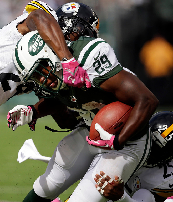 . Pittsburgh Steelers cornerback Ike Taylor (24) and Ryan Clark (25) tackle New York Jets\' Bilal Powell (29) during the first half of an NFL football game on Sunday, Oct. 13, 2013, in East Rutherford, N.J.  (AP Photo/Seth Wenig)