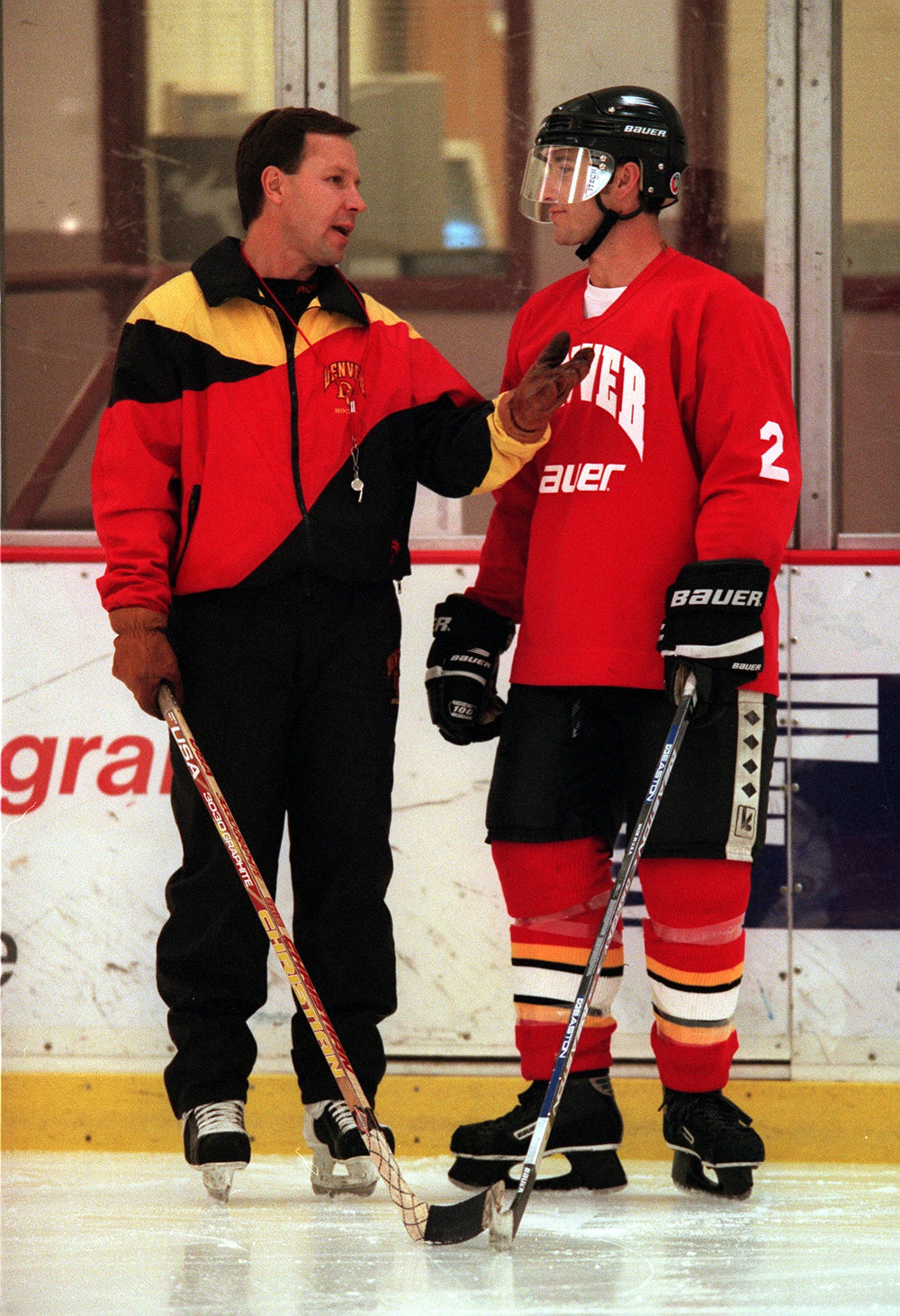 . DU hockey coach George Gwozdecky briefs Denver Post  writer Mike Chambers on practice Wednesday. Chambers was able to  skate with the team this week and participate in a number of  drills.  Photo by KARL GEHRING/THE DENVER POST