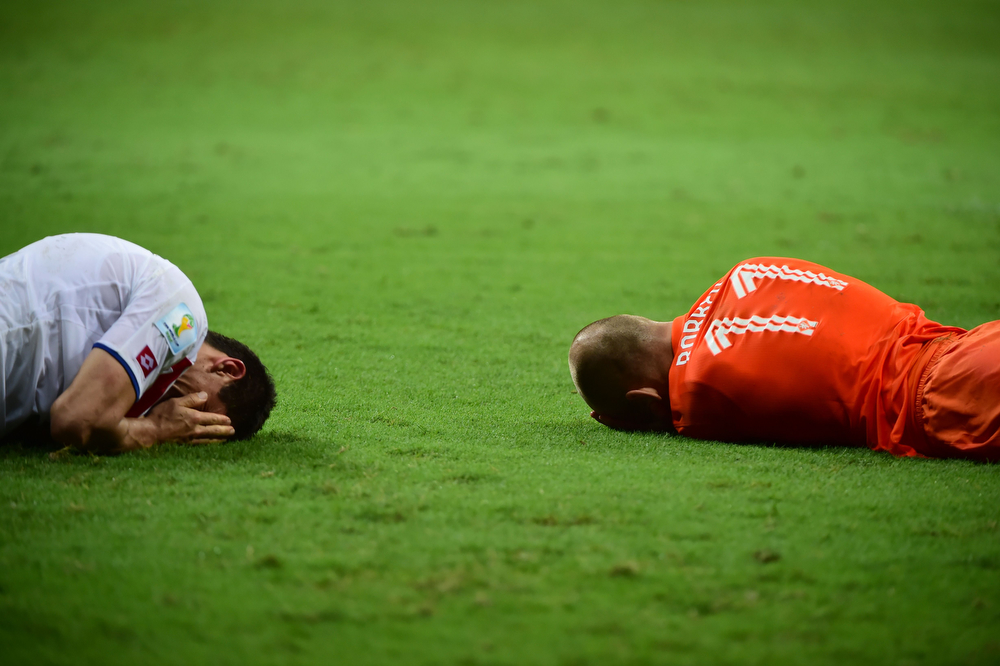 . Costa Rica\'s defender Johnny Acosta (L) and Netherlands\' forward Arjen Robben lie on the pitch following a tackle during the second period of extra time in the quarter-final football match between the Netherlands and Costa Rica at the Fonte Nova Arena in Salvador during the 2014 FIFA World Cup on July 5, 2014. (RONALDO SCHEMIDT/AFP/Getty Images)