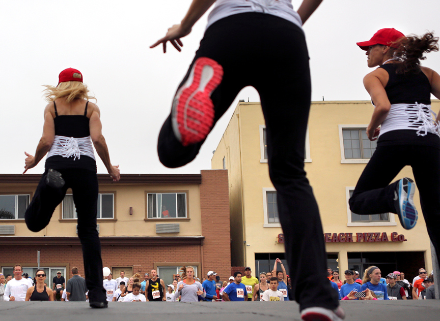 . Runners are led in warm up dance along Beach Street in Santa Cruz on Sunday morning before the start of the 2013 Wharf to Wharf race. (Kevin Johnson/Sentinel)