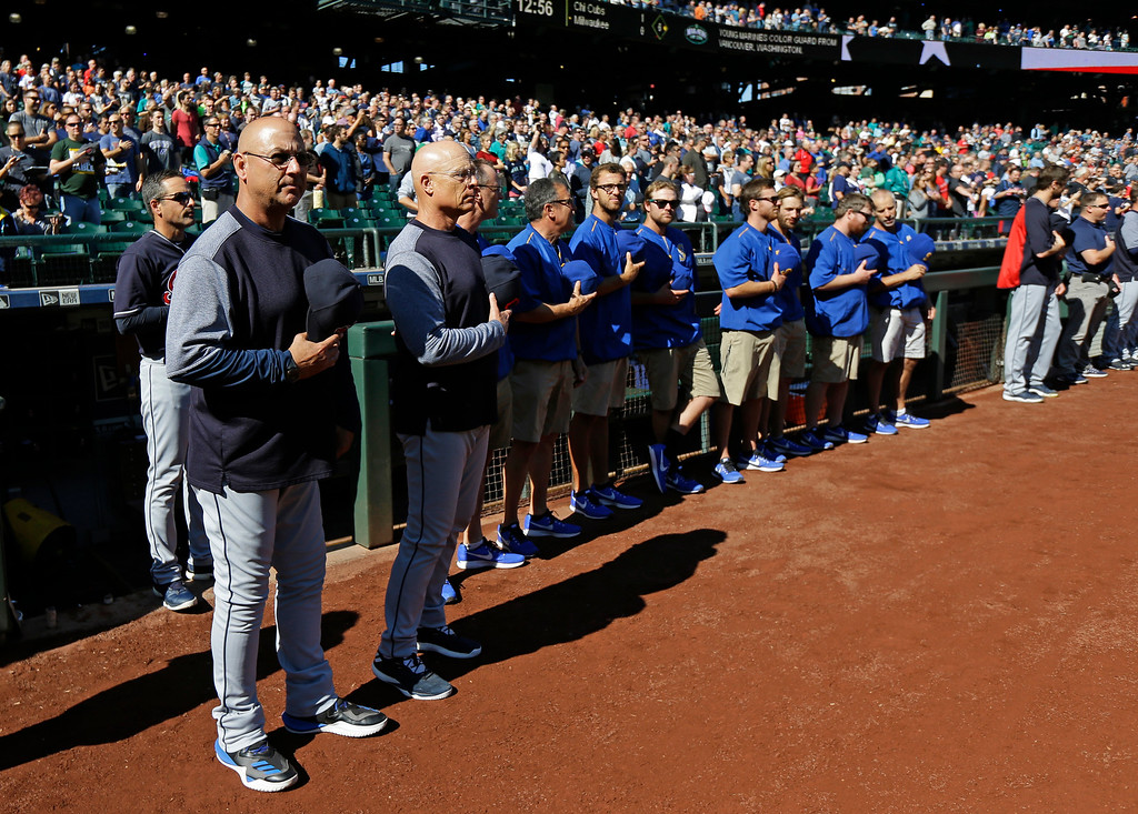 . Cleveland Indians manager Terry Francona, left, and other coaches and players stand during the singing of the national anthem before a baseball game against the Seattle Mariners, Sunday, Sept. 24, 2017, in Seattle. (AP Photo/Ted S. Warren)