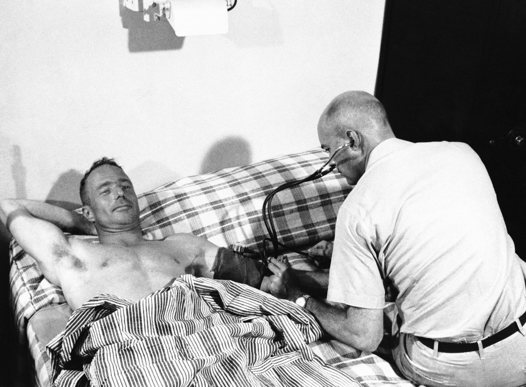 . A doctor checks Scott Carpenter aboard U.S.S. Intrepid after the astronaut was recovered from the ocean, May 24, 1962. The medic is Lt. Col. Evan W. Schear, U.S. Air Force medical corps. (AP Photo)